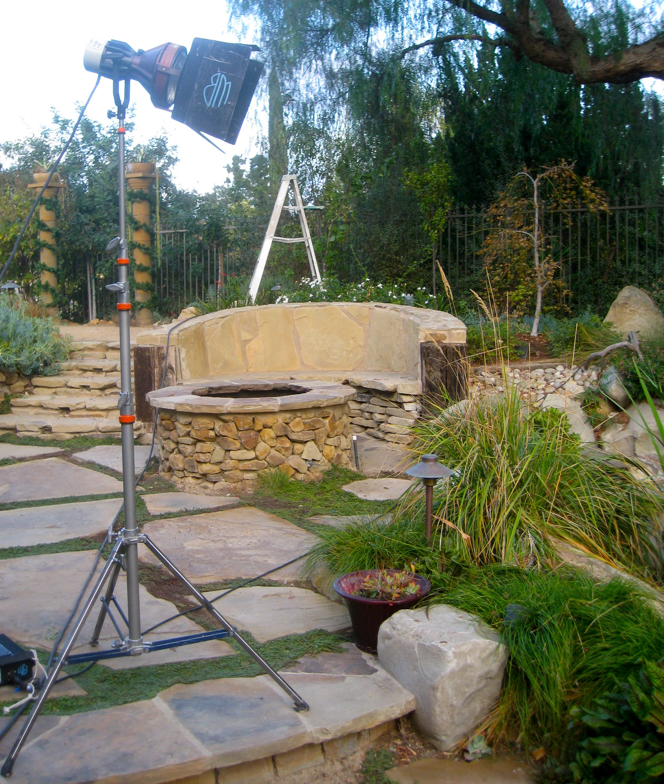 built in semi circular stone bench doubles as a retaining wall in the landscape